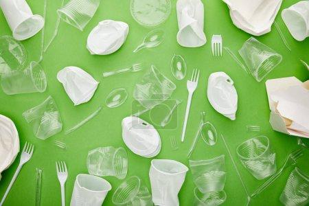 Photo pour Vue supérieure des tasses en plastique froissées, des fourchettes, des plaques et du récipient en carton sur le fond vert - image libre de droit