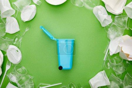Photo pour Vue du dessus de la corbeille bleue entre les gobelets, les fourchettes, les assiettes et le conteneur en carton froissés sur fond vert - image libre de droit