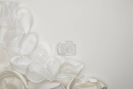 Photo for Top view of crumpled plastic cups and plates white background with copy space - Royalty Free Image
