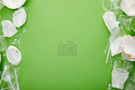 Photo pour Vue supérieure des tasses en plastique froissées et du récipient en carton sur le fond vert avec l'espace de copie - image libre de droit