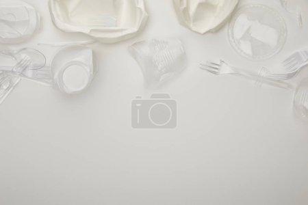 Photo pour Vue supérieure des tasses, des assiettes, des fourchettes et des cuillères en plastique froissés sur le fond blanc avec l'espace de copie - image libre de droit