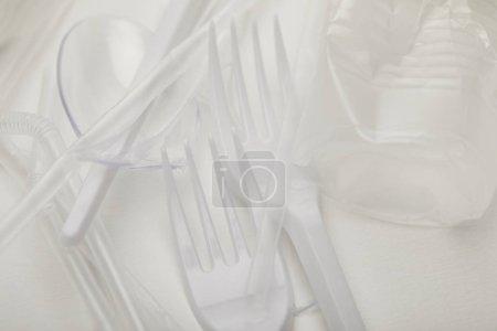 Photo pour Fermer vers le haut la vue de la tasse en plastique froissée, des fourchettes et des cuillères sur le fond blanc - image libre de droit