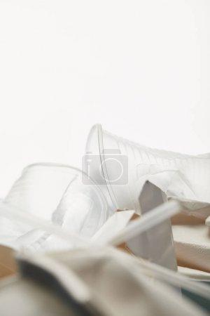 Photo pour Fermer vers le haut de la vue des tasses en plastique transparentes dans le tas des ordures sur le fond blanc - image libre de droit