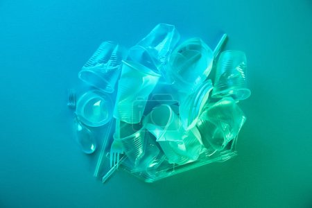 top view of pile of crumpled plastic bags, cups, straws and forks with copy space in blue light