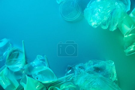 top view of crumpled plastic bags, cups, straws and forks in blue light