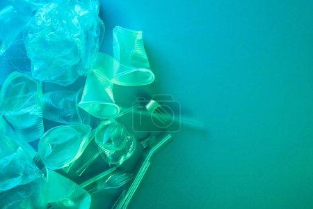 Foto de Vista superior de bolsas de plástico arrugadas, tazas, pajitas y horquillas con espacio de copia en luz azul - Imagen libre de derechos