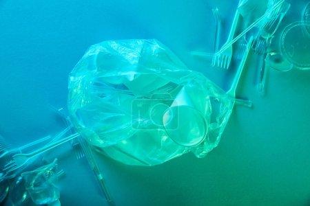 Photo pour Vue du haut du sac en plastique froissé, tasses et fourchettes dans la lumière bleue - image libre de droit