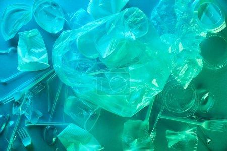 Foto de Vista superior de bolsas de plástico arrugadas y tazas en azul claro - Imagen libre de derechos