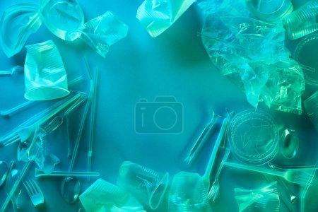 Photo pour Vue du haut des sacs en plastique froissés, tasses et déchets en carton dans la lumière bleue - image libre de droit
