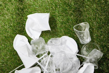 Photo for Top view of pile of crumpled plastic bags, cups and cardboard rubbish on grass - Royalty Free Image
