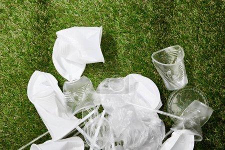 Photo pour Vue supérieure de la pile des sacs en plastique froissés, des tasses et des ordures en carton sur l'herbe - image libre de droit