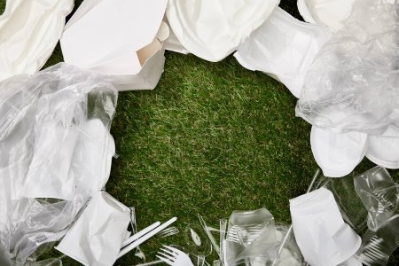 Photo for Top view of crumpled plastic bags, cups and cardboard rubbish on grass with copy space - Royalty Free Image