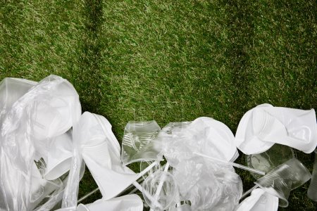 Photo for Top view of crumpled plastic and cardboard rubbish on grass with copy space - Royalty Free Image