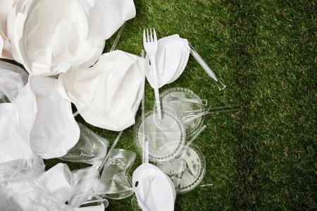 Foto de Vista superior de plástico arrugado y basura de cartón en la hierba - Imagen libre de derechos