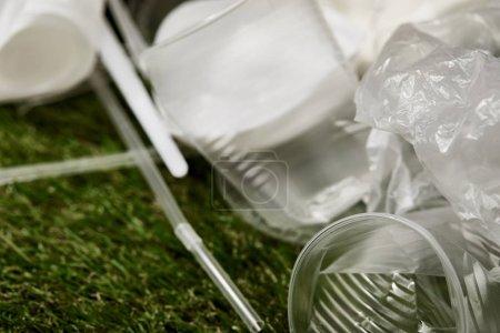 Photo pour Vue rapprochée des gobelets et sacs en plastique froissés sur l'herbe - image libre de droit