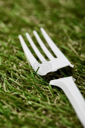 Photo for Close up view of broken disposable plastic fork on green grass - Royalty Free Image