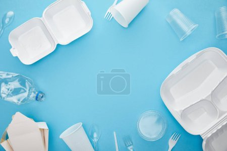 Photo for Top view of plastic and cardboard disposable rubbish on blue background with copy space - Royalty Free Image