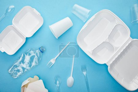 top view of plastic and cardboard rubbish on blue background