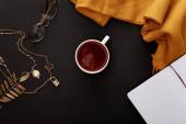 """Постер, картина, фотообои """"верхний вид чая в кружке возле осенних аксессуаров и пустой ноутбук на черном фоне"""""""
