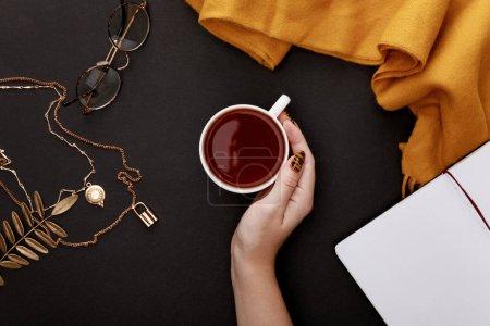 Photo pour Vue partielle de la main féminine près du thé dans une tasse et accessoires automnaux sur fond noir - image libre de droit
