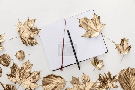 top view of golden foliage near blank notebook with pencil on white background