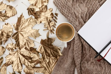 Photo for Top view of knitted brown sweater, coffee, blank notebook and golden foliage on white background - Royalty Free Image