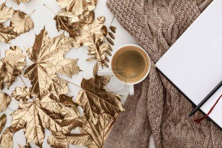 Photo pour Vue du haut du pull marron tricoté, café, carnet vierge et feuillage doré sur fond blanc - image libre de droit