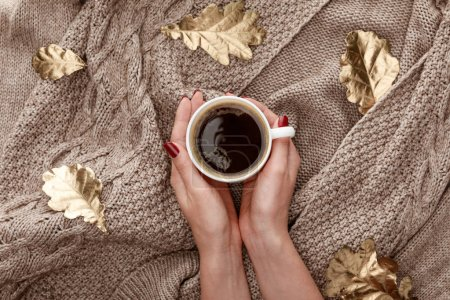 vue partielle de la femme tenant tasse avec café sur chandail brun tricoté avec des feuilles dorées