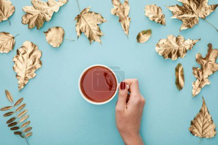 Photo for Cropped view of woman holding tea in mug near golden foliage on blue background - Royalty Free Image