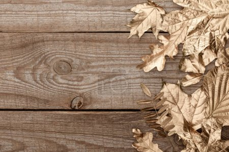 Photo for Top view of golden foliage on wooden textured background - Royalty Free Image