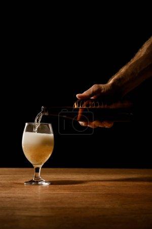 Photo pour Vue partielle de l'homme versant de la bière dans une bouteille en verre sur une table en bois isolée sur noir - image libre de droit
