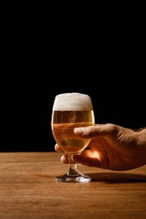 частичный вид человека, держащего стакан пива, изолированный на черном