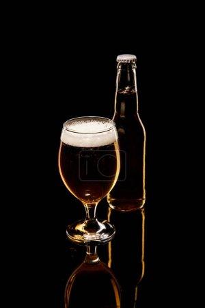 Photo pour Bouteille et verre de bière avec la mousse blanche et les bulles d'isolement sur le noir - image libre de droit
