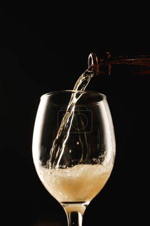 Photo pour Bière coulant de la bouteille dans le verre isolé sur noir - image libre de droit