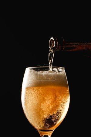 Photo pour Bière coulant de la bouteille dans le verre et faisant la mousse d'isolement sur le noir - image libre de droit