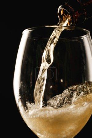 Photo pour Bière coulant de la bouteille dans le verre avec éclaboussure isolé sur noir - image libre de droit