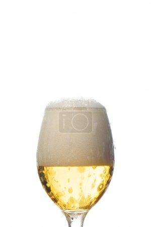 verre mouillé de bière avec mousse blanche isolé sur blanc
