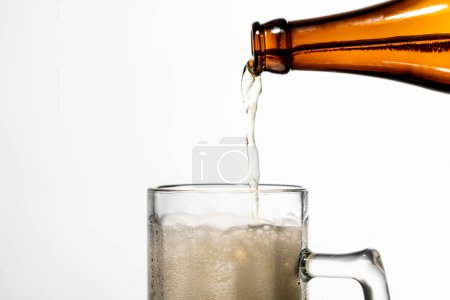 Photo pour Bière versant de la bouteille dans le verre avec la mousse blanche d'isolement sur le blanc - image libre de droit