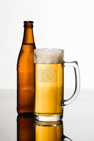 Photo for Glass of beer with foam near wet bottle isolated on white - Royalty Free Image