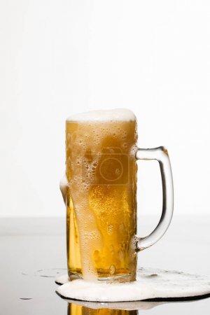 Photo pour Verre humide de bière avec la mousse et la flaque d'eau sur la surface isolée sur le blanc - image libre de droit