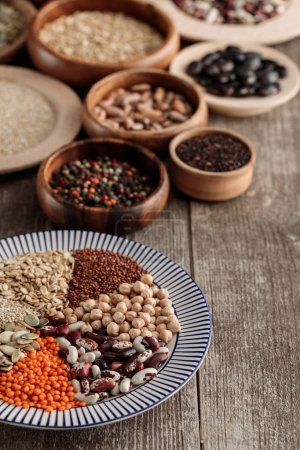 Photo for Wooden and ceramic plates with legumes and cereals on table - Royalty Free Image
