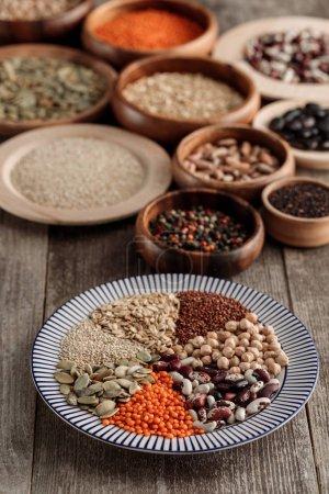 Photo pour Assiette rayée de lentilles, haricots, pois chiches, céréales et graines de citrouille près des bols en bois sur la table - image libre de droit
