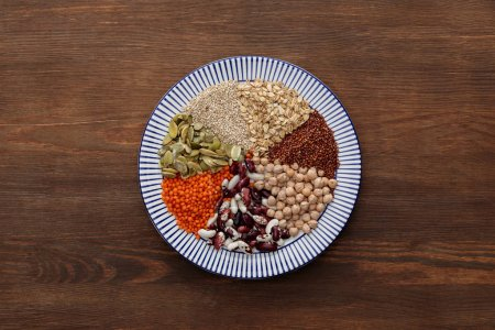 Photo for Top view of striped plate with raw lentil, chickpea, quinoa, oatmeal, beans and pumpkin seeds on wooden table - Royalty Free Image