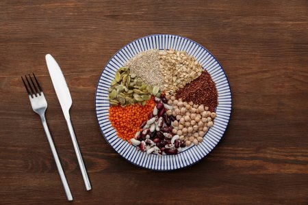 Photo for Top view of fork and knife near striped plate with raw lentil, chickpea, quinoa, oatmeal, beans and pumpkin seeds on wooden surface - Royalty Free Image