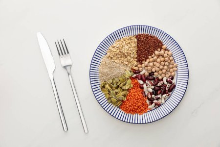Photo for Top view of fork and knife near striped plate with raw lentil, chickpea, quinoa, oatmeal, beans and pumpkin seeds on marble surface - Royalty Free Image
