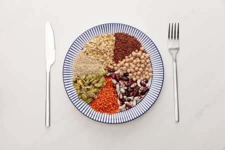 Photo for Top view of striped plate with raw lentil, chickpea, quinoa, oatmeal, beans and pumpkin seeds near cutlery on marble surface - Royalty Free Image