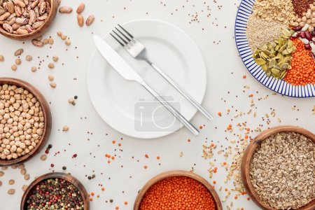Photo for Top view of empty plate with fork and knife near bowls with raw lentil, quinoa, oatmeal, beans, peppercorns and pumpkin seeds on marble surface with scattered grains - Royalty Free Image