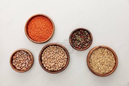 Photo for Top view of wooden bowls with red lentil, beans, chickpea, oatmeal and peppercorns on white marble surface - Royalty Free Image