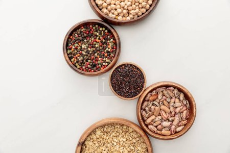 Photo for Top view of wooden bowls with black quinoa, oatmeal, beans, peppercorns and chickpea on white marble surface - Royalty Free Image