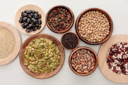 Photo pour Vue de dessus des bols en bois avec divers haricots, quinoa, grains de poivre, graines de citrouille et pois chiche sur la surface de marbre blanc - image libre de droit